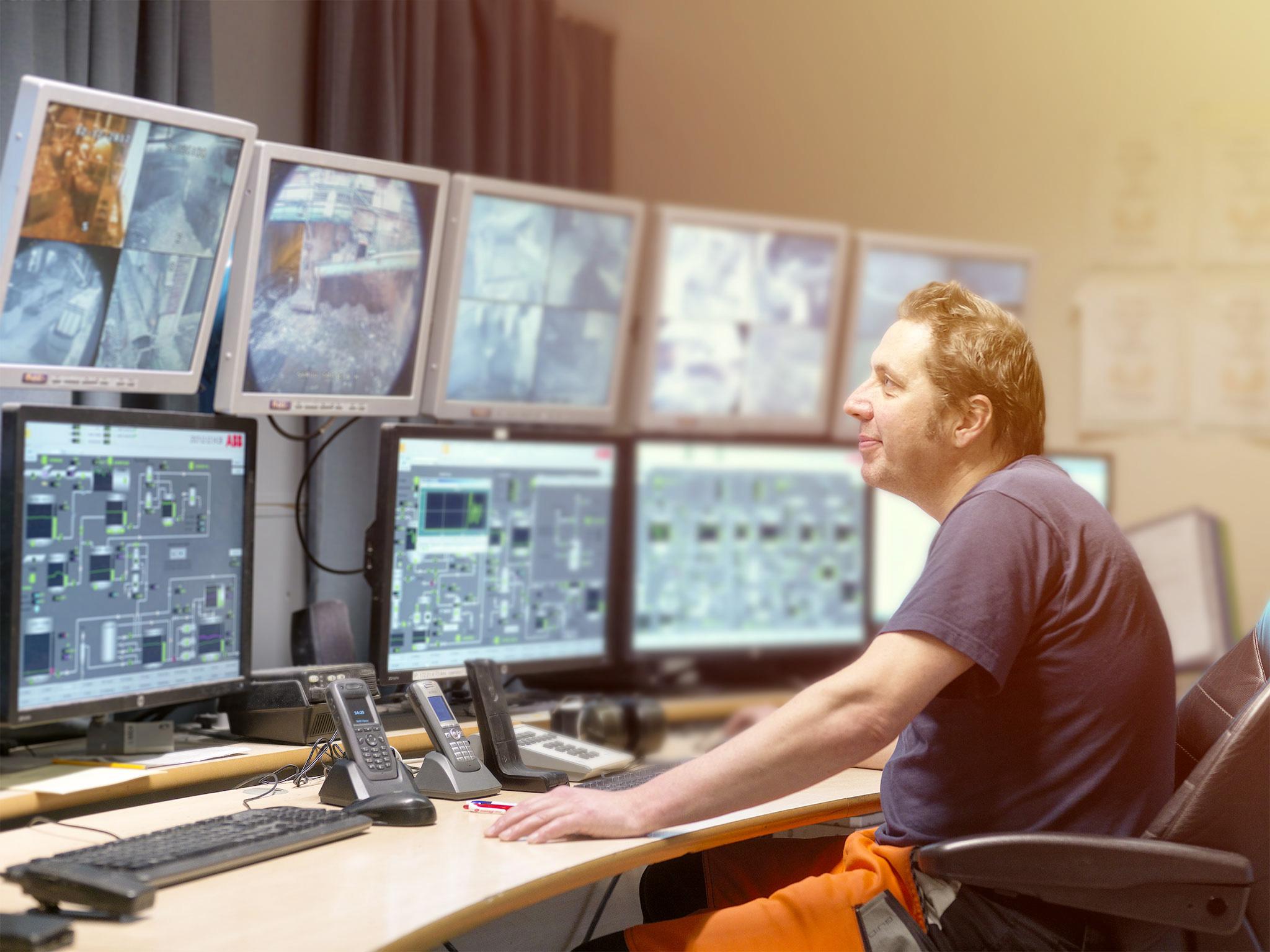 Anställd kontrollerar flera bildskärmar.